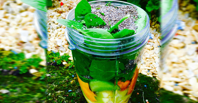 Ingredients for a green smoothie inside a jar with chia seeds on top